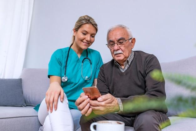 Ayuda de cuidado ayudando a hombre mayor aprendiendo a usar el teléfono celular