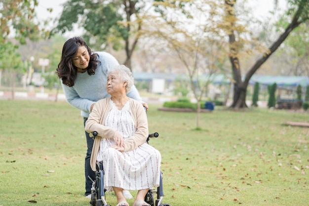 Ayuda y cuidado paciente mujer asiática senior sentado en silla de ruedas en el parque.