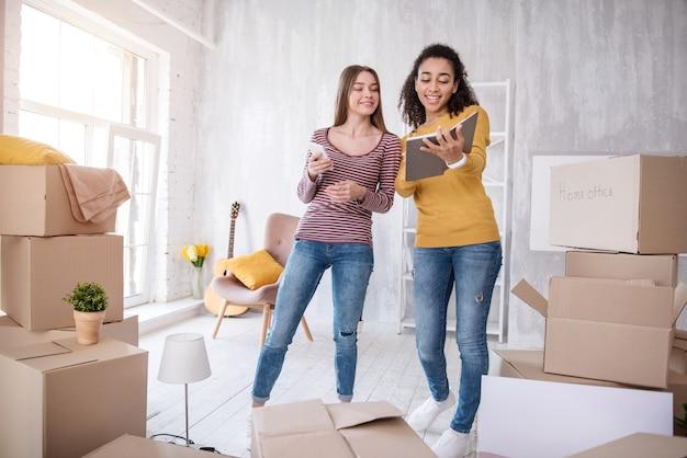 Ayuda necesaria. chicas jóvenes alegres que buscan el número de teléfono de las mudanzas, que necesitan ayuda para salir del dormitorio