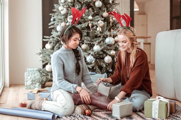 Ayudándose unos a otros. chica agradable atento en orejas de ciervo sentados en el suelo rodeado de materiales con árbol decorado detrás del concepto de navidad