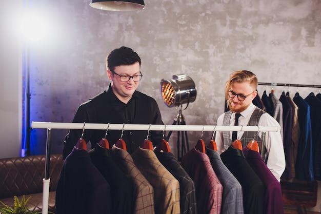 Ayudante de tienda ayudando al hombre a elegir una chaqueta