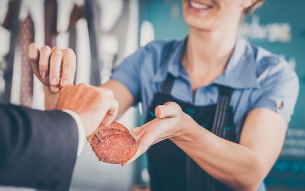 Ayudante de tienda dando carne al cliente