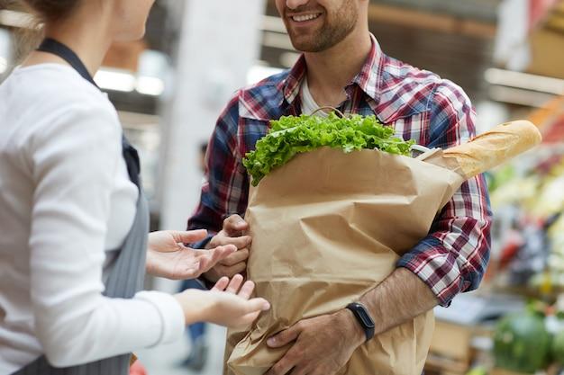 Ayudante de tienda hablando con el cliente closeup