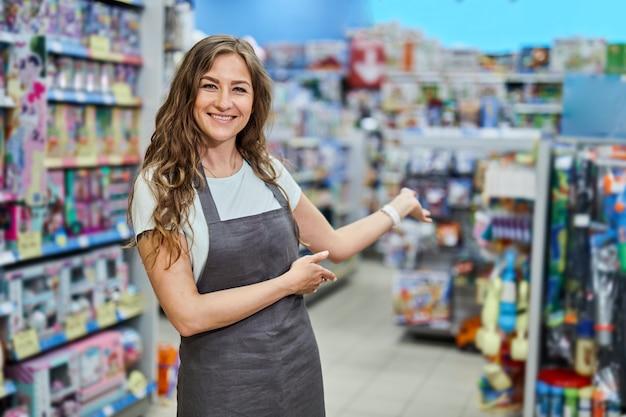 Ayudante de tienda de sexo femenino alegre atractivo que sonríe a la cámara que se coloca en tienda.