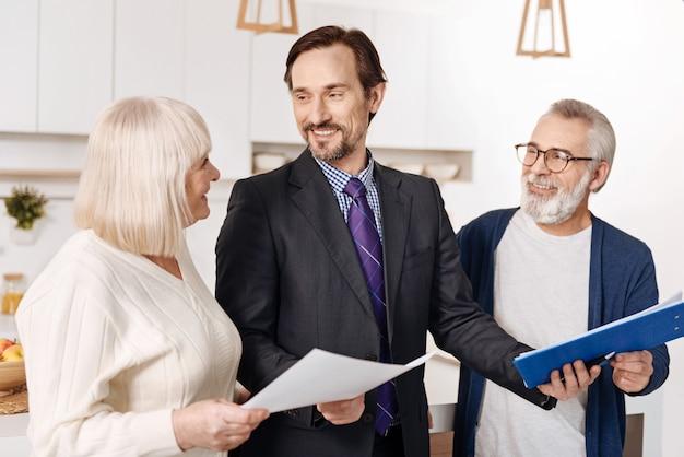 Ayudar a las personas en cuestiones legales. asesor legal positivo experimentado que se reúne y presenta un contrato a la pareja de ancianos mientras expresa felicidad