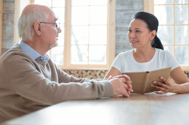 Ayudar a las personas. hermoso voluntario feliz sosteniendo el libro mientras habla con el hombre mayor y lo mira