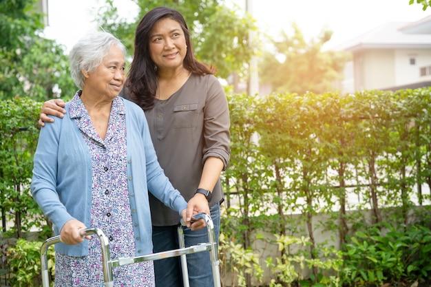 Ayude y cuide a la mujer mayor asiática del uso del andador en el parque.