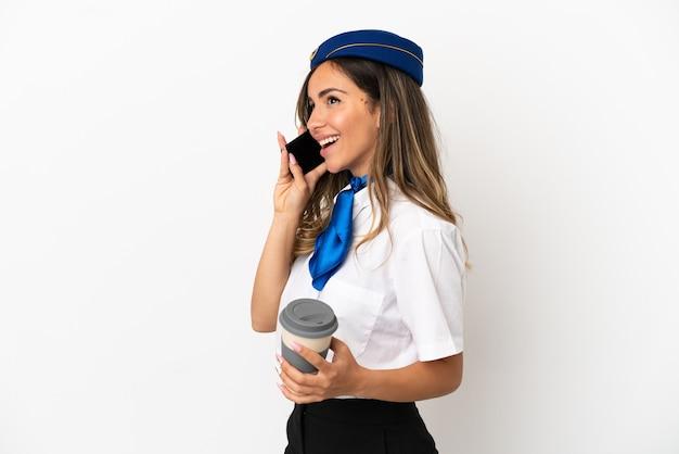 Azafata de avión sobre fondo blanco aislado sosteniendo café para llevar y un móvil