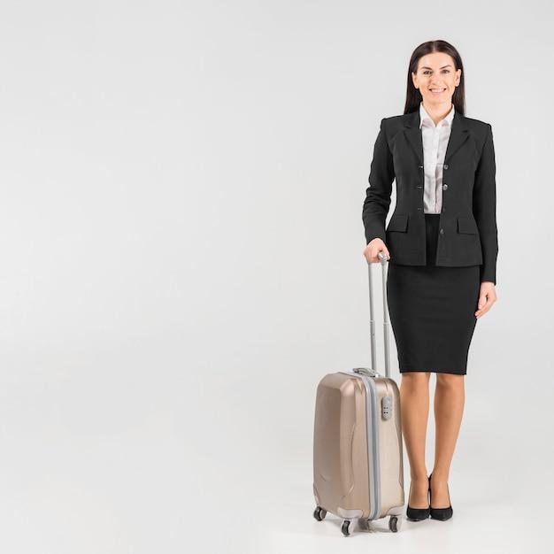 Azafata de uniforme con maleta.