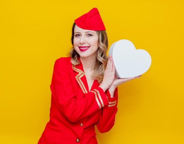 Azafata en uniforme rojo con caja de gfit de vacaciones en forma de corazón