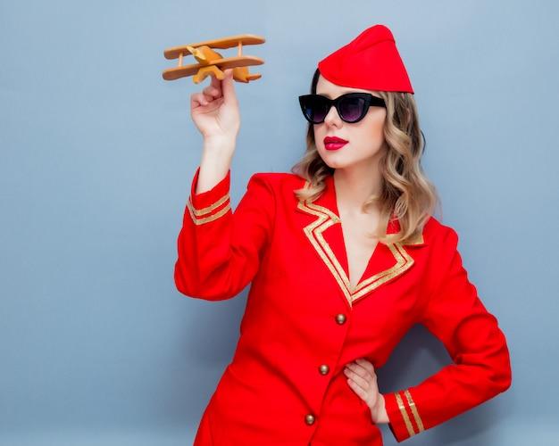 Azafata vestida de rojo uniforme con avión de madera
