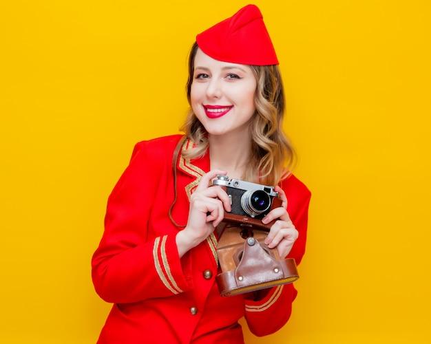 Azafata vestida con uniforme rojo con cámara de fotos