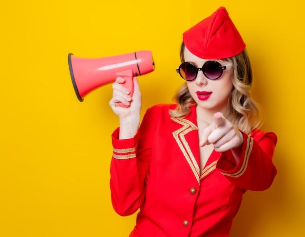 Azafata vintage vistiendo en uniforme rojo con megáfono