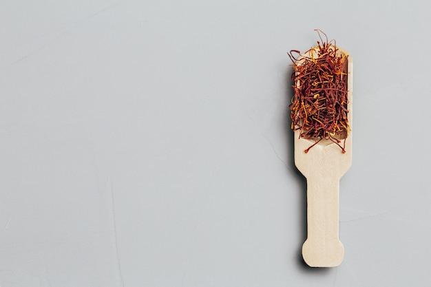 Azafrán en una cuchara sobre un fondo gris