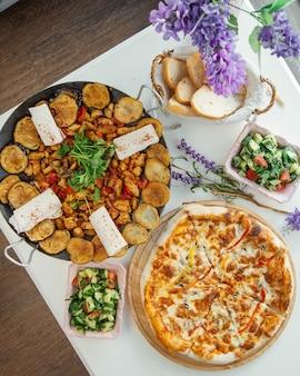 Azerbaiyán sac ichi con pizza y ensalada verde.
