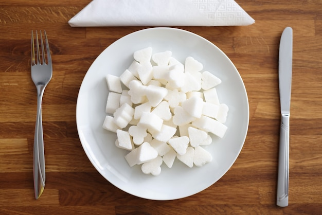 El azúcar blanco se encuentra en la placa junto al tenedor y el cuchillo