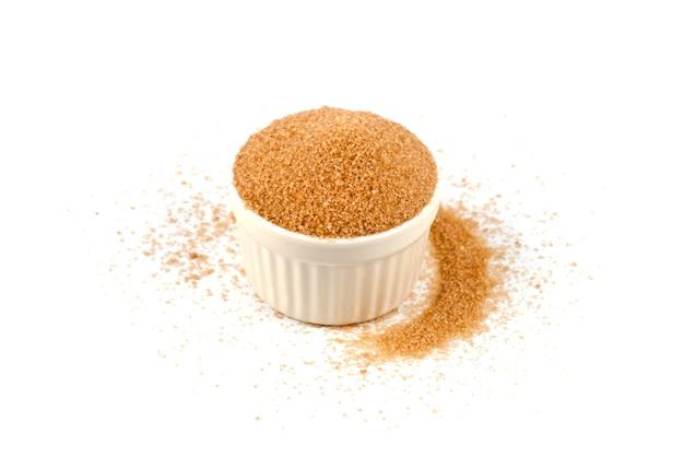 Azúcar de caña de brown en el cuenco de cerámica aislado en el fondo blanco.