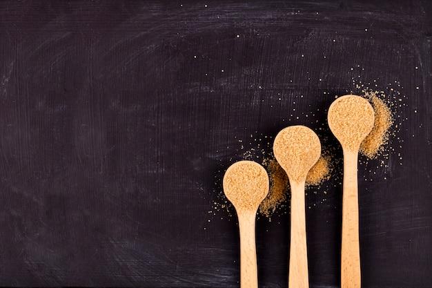 Azúcar de caña de brown en tres cucharas de madera en fondo negro.