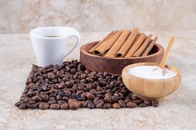 Azúcar, canela en rama, granos de café y una taza de café.