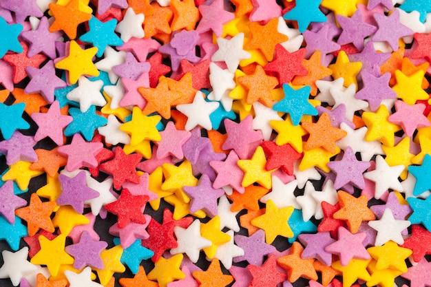 El azúcar de caramelo en forma de estrella de color rocía como fondo