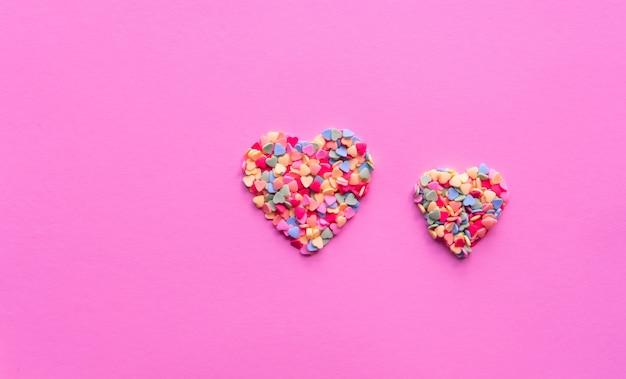 El azúcar colorido en forma de corazón asperja en fondo rosado vivo. concepto de día de san valentín