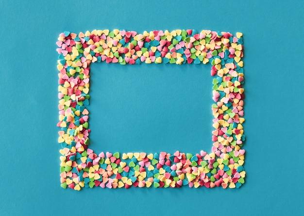 El azúcar colorido en forma de corazón asperja el marco en fondo azulverde. concepto de día de san valentín