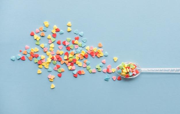 El azúcar colorido en forma de corazón asperja sobre fondo azul. concepto de día de san valentín