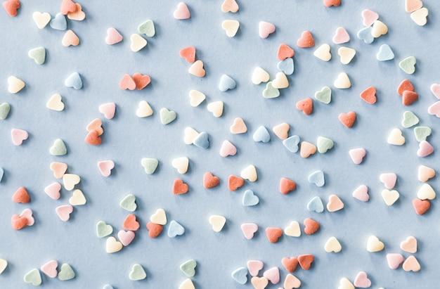 El azúcar colorido en forma de corazón rocía sobre fondo azul pastel. concepto de día de san valentín