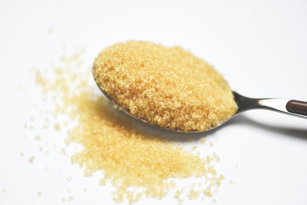 Azúcar moreno en una cuchara en blanco