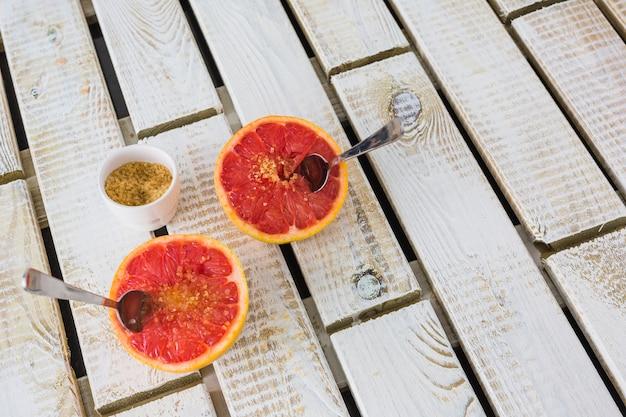 Azúcar moreno con pomelo a la mitad con una cuchara sobre fondo de madera