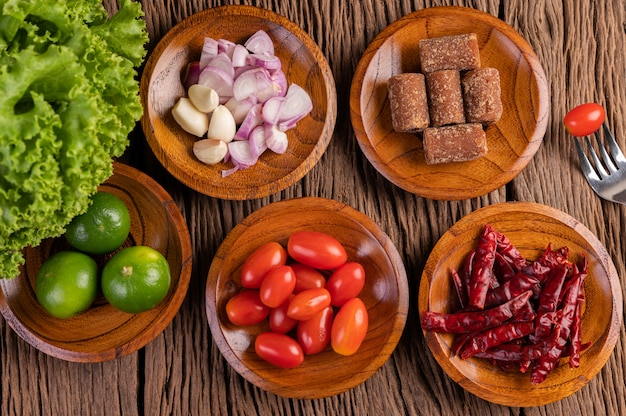 Azúcar de palma, cebollas rojas, pimientos secos, tomates, pepinos, judías largas y lechuga en un tazón.