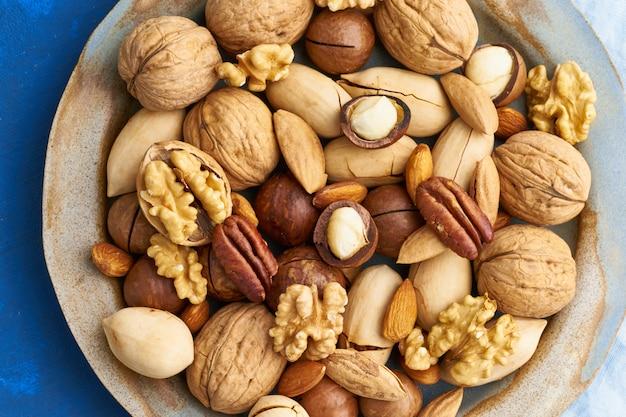 Azul clásico en la comida. mezcla de nueces en el plato: nuez, almendras, nueces, macadamia