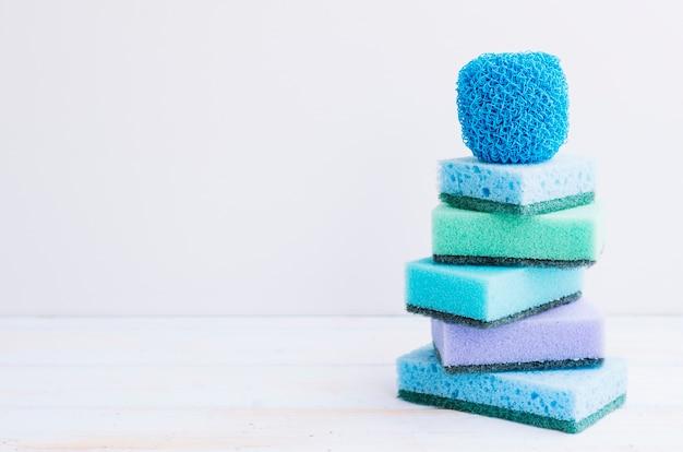 Azul; esponjas verdes y púrpuras en el escritorio de madera contra la pared