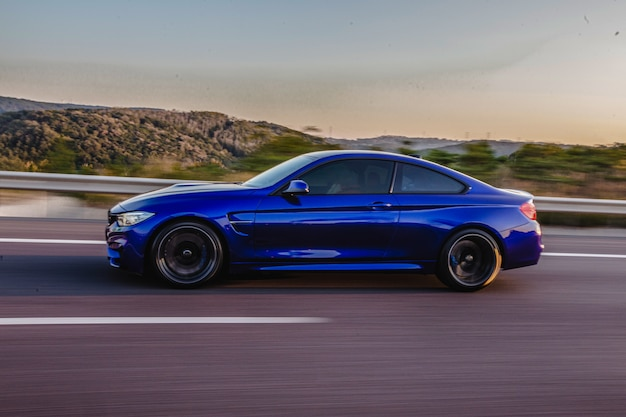 Azul marino coupé deportivo en la carretera, vista lateral.