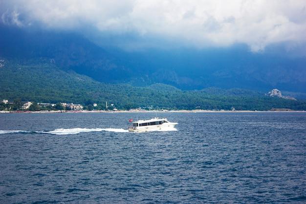 Azul tranquilo mar mediterráneo, montañas y yate blanco.
