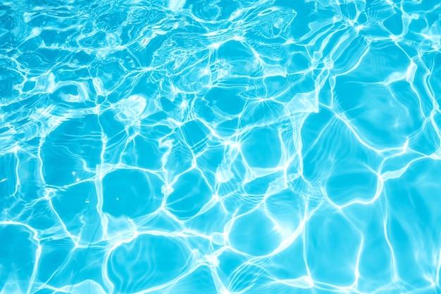 Azul y brillante superficie del agua y ola ondulada con reflejo del sol en la piscina