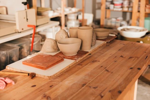 Azulejos artesanales y vajilla de barro sobre mesa de madera en el taller.