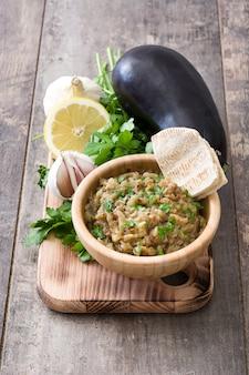 Baba ganoush en tazón de madera y pan de pita en mesa de madera