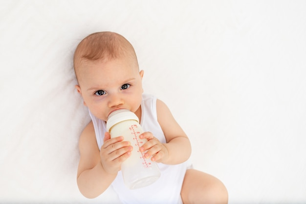 Baby boy 8 meses acostado en la cama en la guardería de espaldas y sosteniendo una botella de leche, alimentando al bebé, el concepto de comida