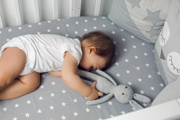 Baby boy acostado en una cama redonda con un juguete de conejo tejido