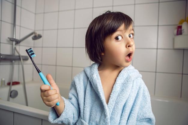 Baby boy en un baño blanco se encuentra en una bata azul y sostiene un cepillo de dientes en su mano