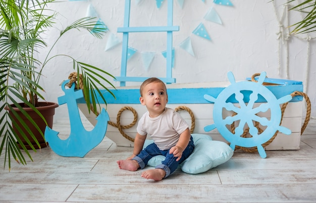 Baby boy en camiseta blanca y jeans sentado mirando hacia arriba