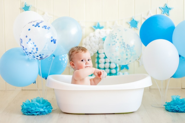 Baby boy celebra su cumpleaños 1 año en un baño con globos, bañando al bebé con globos azules