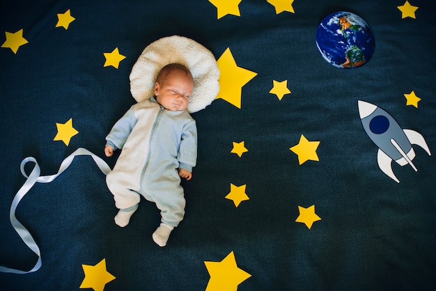 Baby boy está dormido y se sueña a sí mismo como un astronauta en el espacio