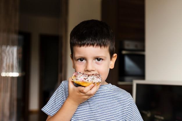 Baby boy con dulce donut en casa