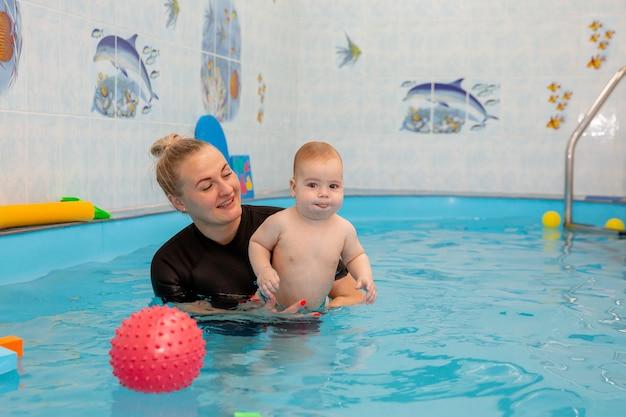 Baby boy entrena para nadar en la piscina con un entrenador