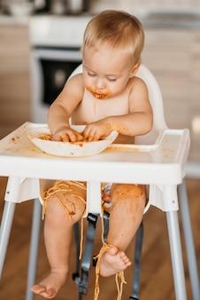 Baby boy haciendo un lío con pasta