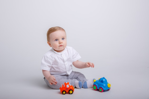 Baby boy jugando con coches de juguete sobre fondo blanco.