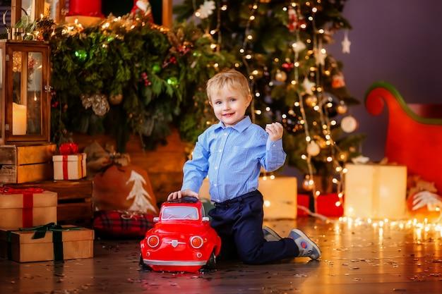 Baby boy niño rubio junto al árbol de navidad