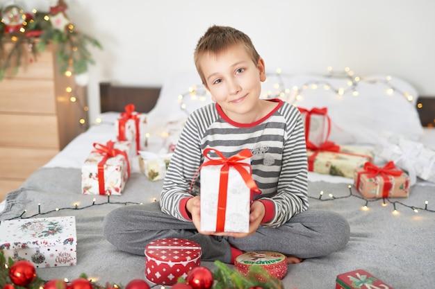 Baby boy con regalos de navidad en casa en la cama con decoración navideña